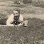 Fotografia przedstawia kobietę leżącą na kocu. Przy niej leży mały pies.