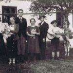 Fotografia przedstawia sześć osób stojących przed domem. Dwie trzymają na rękach psy, jedna - gitarę. Obok stoi koza.