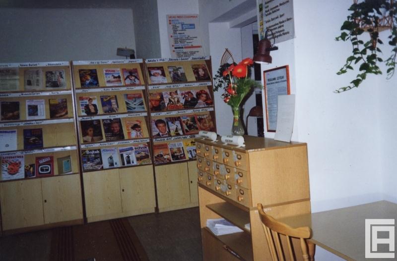 Fotografia przedstawia wnętrze biblioteki. W głębi ekspozytory z czasopismami. Po prawej szufladki z katalogiem, na ścianach regulaminy. Widoczne kwiaty cięte i doniczkowe.