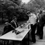 """Fotografia przedstawia dwóch mężczyzn grających w szachy przy jednym ze stolików. Stoły z szachownicami są ustawione w ciągu na wolnym powietrzu - jak do zawodów. Obok jednego z graczy siedzi chłopiec. W tle widoczne inne osoby obserwujące lub przechodzące, tablica z napisem """"tenis"""" oraz drzewa."""