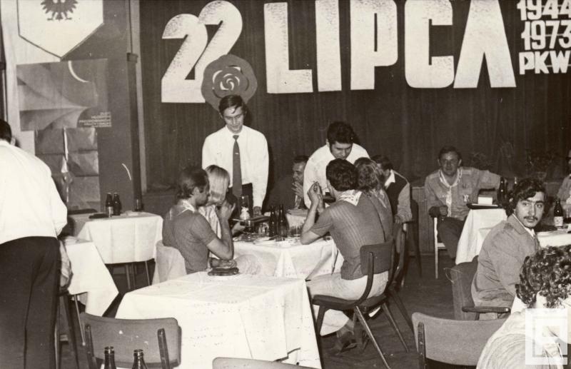 """Fotografia przedstawia ludzi siedzących przy stolikach. Na ścianie napis """"22 lipca, 1944 1973 PKWN"""". Po lewej widoczny plakat """"Zlot Młodych Przodowników Pracy i Nauki""""."""