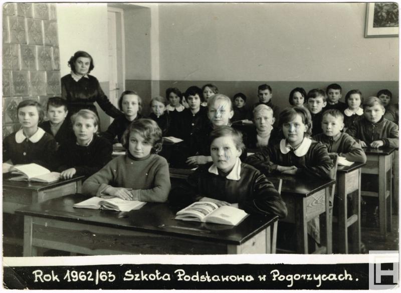 Fotografia przedstawia dwa rzędy ławek szkolnych z uczniami. Z lewej widoczna nauczycielka oraz fragment pieca kaflowego.