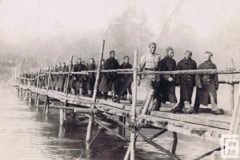 Fotografia przedstawia żołnierzy idących przez drewniany most.